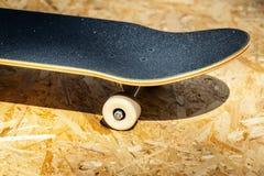 Faites de la planche à roulettes avec les roues blanches sur un fond en bois dans un skatepark Photos libres de droits
