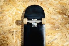Faites de la planche à roulettes avec les roues blanches sur un fond en bois dans un skatepark Image stock