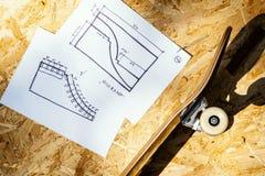 Faites de la planche à roulettes sur un fond en bois avec des plans pour un miniramp dans un skatepark Image libre de droits