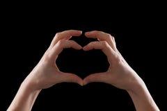 Faites des gestes, jeune femme de mains montrant le symbole du coeur et de l'amour Photographie stock libre de droits