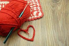Faites du crochet le coeur rouge avec la boule de laine et le tissu de four Photos stock