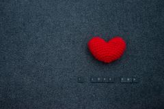 Faites du crochet le coeur rouge sur le fond et l'inscription noirs je t'aime Photos stock