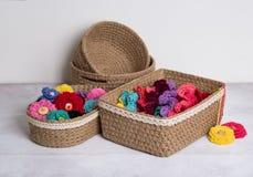 Faites du crochet les paniers avec les fleurs tricotées par couleur sur le fond blanc Images libres de droits