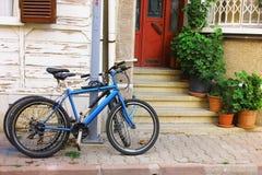 Faites du vélo la position près de l'entrée à la maison Image stock