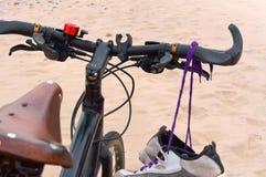 Faites du vélo sur la plage, les espadrilles accrochant sur le vélo, la mer et le vélo Photos libres de droits
