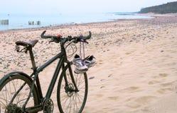 Faites du vélo sur la plage, les espadrilles accrochant sur le vélo, la mer et le vélo Images stock