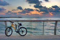 Faites du vélo sur la promenade sur le fond du ciel et de la mer de coucher du soleil. Images stock