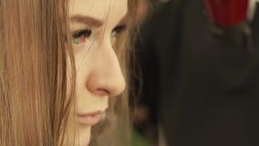 Faites face à la jeune femme pendant les cheveux de hairstyling avec le dessiccateur et la balayez dans le salon de beauté Fermez banque de vidéos