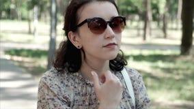Faites face au plan rapproché de la jolie femme de brune dans des lunettes de soleil marchant par le parc d'été clips vidéos