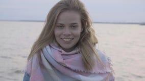 Faites face au portrait de la femme heureuse attirante se tenant au coucher du soleil de fond au-dessus de la mer banque de vidéos