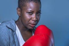 Faites face au portrait de la jeune femme américaine de sport d'africain noir fâché et provoquant dans des gants de boxe s'exerça photos stock