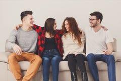 Faites la fête avec des amis, les jeunes s'asseyant sur le divan Photos stock
