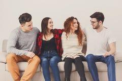 Faites la fête avec des amis, les jeunes s'asseyant sur le divan Photographie stock