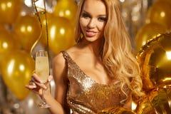 Faites la fête la célébration, jeune femme magnifique dans la robe d'or photo stock