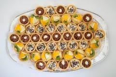 Faites la fête le plateau avec de petits petits gâteaux avec le bourrage différent, restauration de nourriture Photographie stock libre de droits