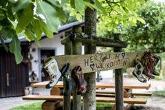 Faites la fête le signe de bottes en caoutchouc de label en bois, accueil de moyens de Herzlich Willkommen de cabane dans un arbr Photographie stock libre de droits