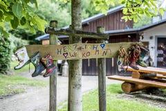 Faites la fête le signe de bottes en caoutchouc de label en bois, accueil de moyens de Herzlich Willkommen de cabane dans un arbr Images libres de droits