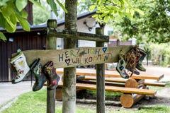 Faites la fête le signe de bottes en caoutchouc de label en bois, accueil de moyens de Herzlich Willkommen de cabane dans un arbr Photos stock