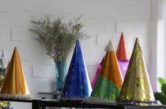 Faites la fête les chapeaux et toute autre substance sur le fond blanc de mur photographie stock