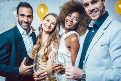Faites la fête les personnes avec des boissons célébrant la nouvelle année ou une fête d'anniversaire Image stock