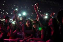 Faites la fête les personnes en cercle d'or à un concert Photographie stock
