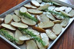 Faites la pomme de terre cuire au four de tranche avec le romarin Image libre de droits