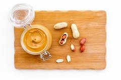 Faites le beurre d'arachide Pâte dans le pot en verre sur le bureau de coupe près de l'arachide sur l'espace blanc de copie de vu images libres de droits