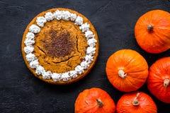 Faites le tarte de potiron Gâteau entier près des potirons sur la vue supérieure de fond noir images libres de droits