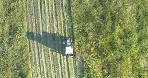 Faites les foins les mouvements de presse le long du champ laissant le chemin de l'herbe coupée banque de vidéos
