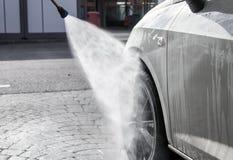 Faites pression sur le jet d'eau au-dessus du pneu de voiture à la station de lavage Photos stock