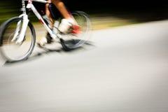 Faites signe le cycliste brouillé allant rapidement sur une ruelle de vélo de ville image libre de droits