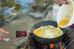 Faites une omelette sur la casserole en huile chaude, la placez sur le fourneau, préparez le petit déjeuner pour augmenter ou cam Photo libre de droits
