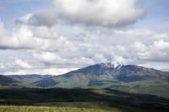 Faites une pointe avec les montagnes couvertes par neige de l'Utah avec rouler les collines vertes Images libres de droits