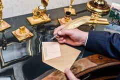 Faites varier le pas du stylo avec l'encrier encastré et les papiers blancs sur le fond en bois Photographie stock libre de droits