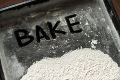 Faites Word cuire au four écrit sur la plaque de cuisson couverte de la farine blanche Photo stock