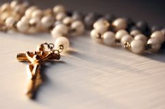 Faith. Macro shot of a beaded necklace with a cross Stock Photography