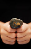 Faith. A stone is engrave with the word \Faith\ and is held by both hands Stock Photos