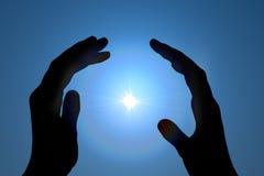 Faith. Hands protecting energy spark against a blue sky Stock Photo