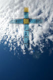 Faith. Blue and yellow cross in stained glass emerging from a cloud in the blue sky, symbolising hope and faith; copy space Stock Images