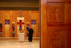 Faith. Priest saying a prayer in front of the altar Stock Photos