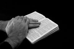 Faith. Touching black and white image of a hand of man resting on bible, reading the book of saint matthew, on black background Royalty Free Stock Photo