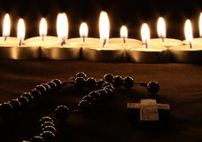 Faith. A crucifix in front of a row of candles Royalty Free Stock Images