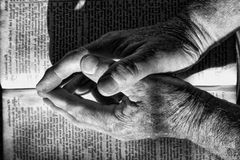 Faith. Praying hands folded on a bible with dramatic lighting Royalty Free Stock Photography