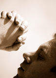 Faith. Cropped image of a young man praying on a light background (monochrome Stock Photography