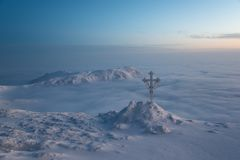 Faith is above all. Frosted cross Christianity symbol against beautiful sunrise scene in mountains Stock Images