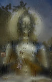 Faith abstract with buddha statue and rain drop on the window. Stock Photo