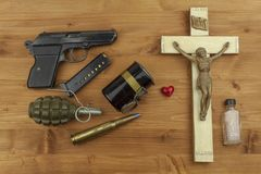 Faith against violence. A wooden crucifix with the lettering INRI and guns. Stock Photography