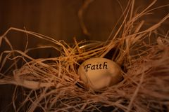 Faith easter egg in straw bed stock photography