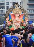 Faith in God. Devotees carry statue of hindu god Ganesha in a process for immersing in holy water at the end of 11 day Ganpati festival in India Stock Image