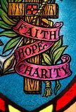 Faith hope and charity. Stained glass window with faith hope and charity inscribed stock image